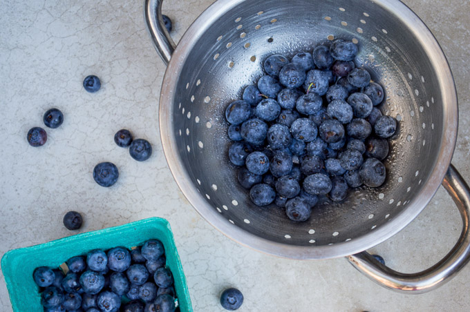 blueberries in a strainer with aqua container of blueberries