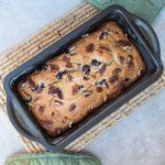 blueberry banana bread in a metal pan with green oven mitts