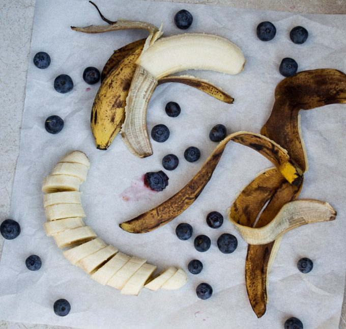 cut up banana with banana peel and blueberries
