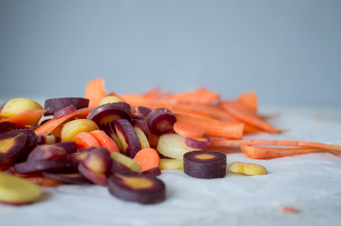 side view of carrots sliced vertically and rainbow carrots sliced into coins