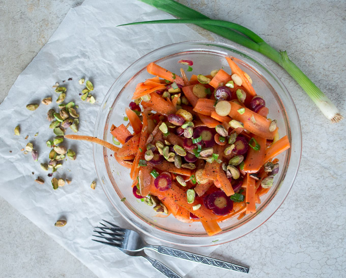 Carrot salad in a glass bowl with chopped pistachios, green onions, and two forks