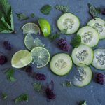 cut cucumbers, limes, blackberries, and mint leaves on slate tile.
