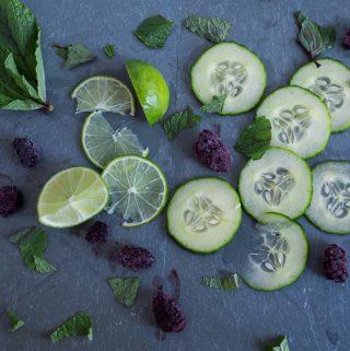 cut cucumbers, limes, blackberries, and mint leaves on slate tile.