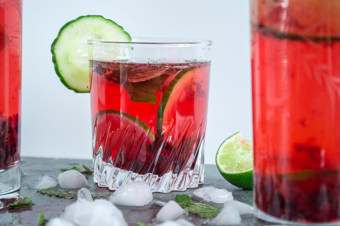 glass of mojito on slate tile with ice, limes, cucumbers, and blackberries