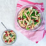 asparagus pasta salad in glass bowl with a red towel