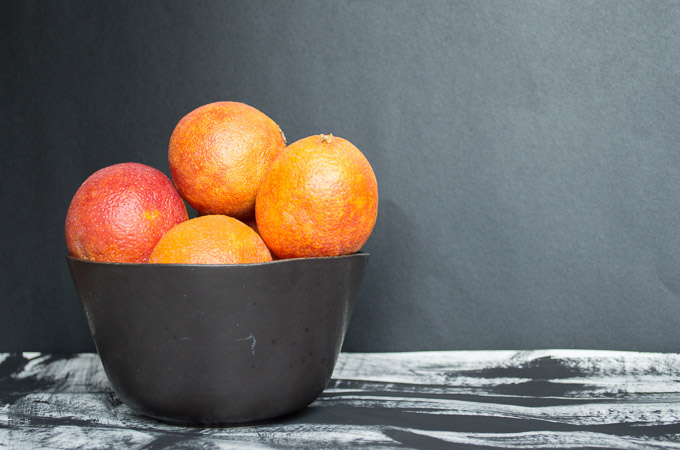 four blood oranges in a black bowl