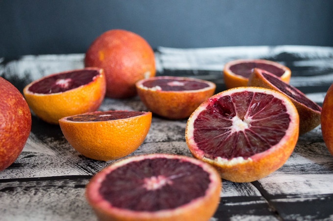 three blood oranges sliced in half with one whole orange