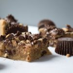 chocolate peanut butter blondie squares with peanut butter cups on a white background