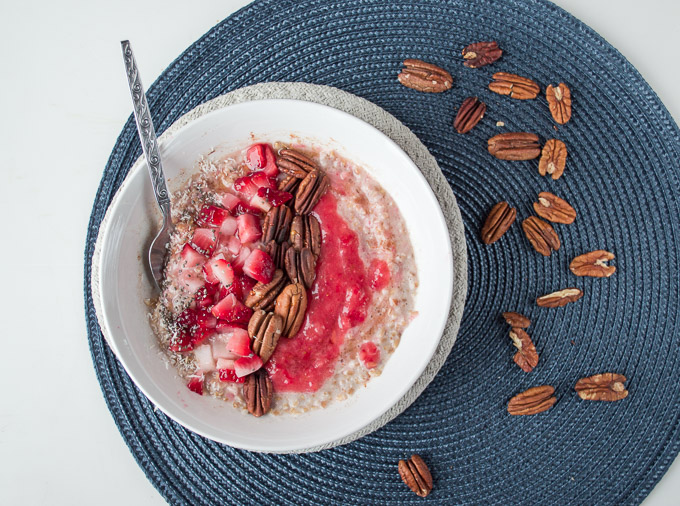 bowl of strawberry and cream oatmeal with pecans on a blue place mat