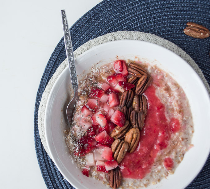 close up of strawberry and cream oatmeal in a white bowl