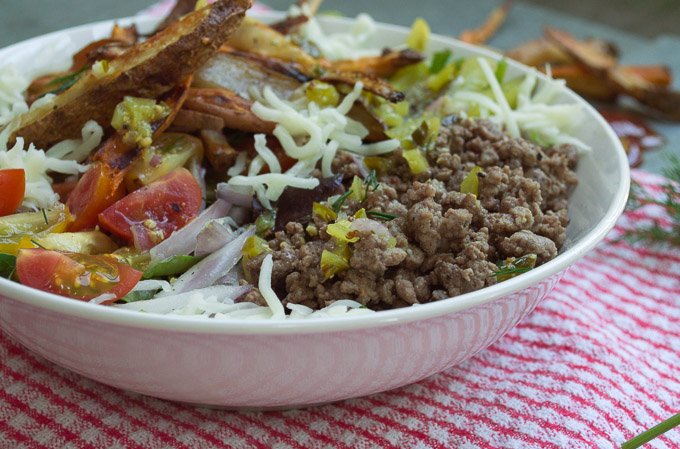 side view of burger salad in a white bowl