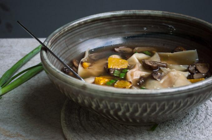 butternut squash wonton soup in a black bowl