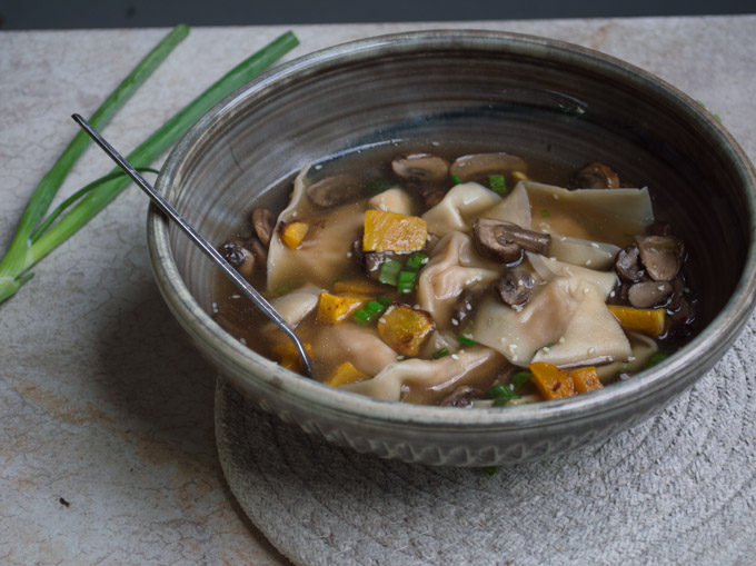 butternut squash wonton soup with green onions in a black bowl