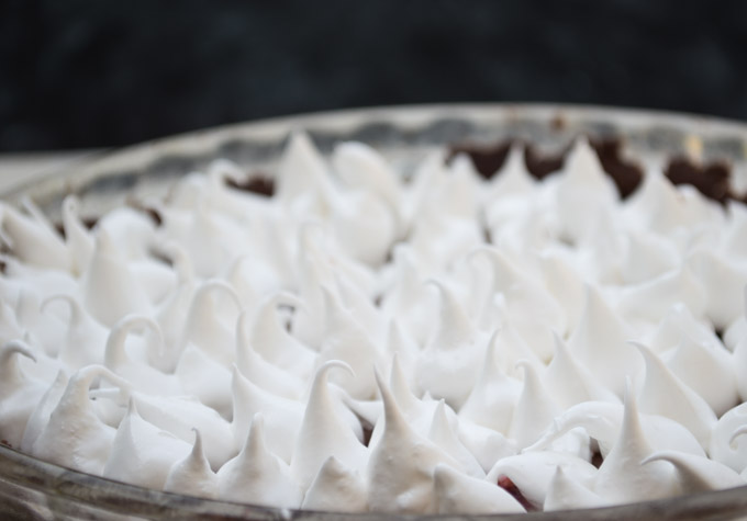 meringue frosting on chocolate raspberry tart