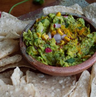 guacamole in a small bowl with tortilla chips