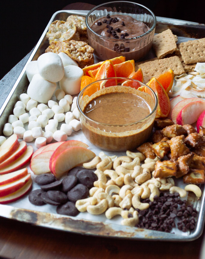 angle view of dessert board with dips, treats, and fruit