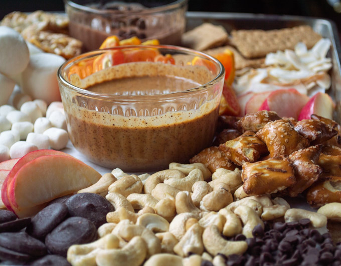 close view of dessert board with dips, sweets, and fruit