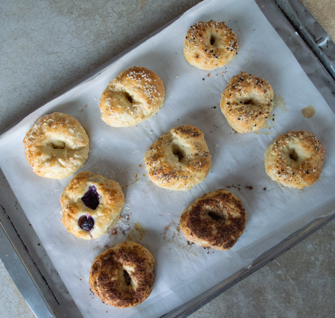 cooked bagels with toppings on a parchment paper baking sheet