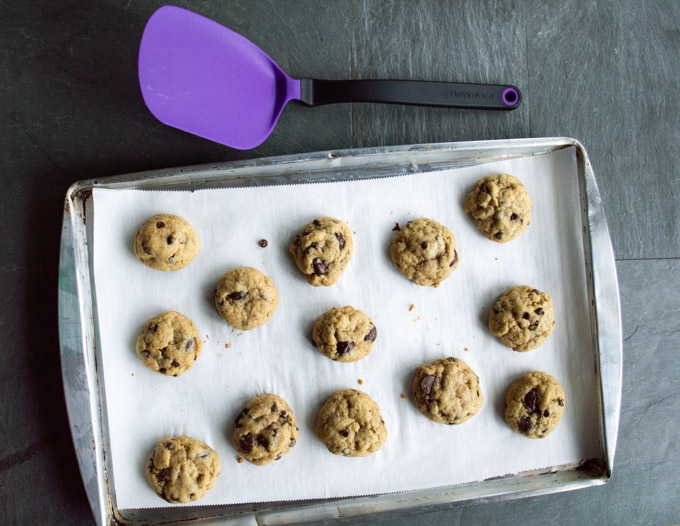 Cooled cookies on a baking sheet with purple spatula