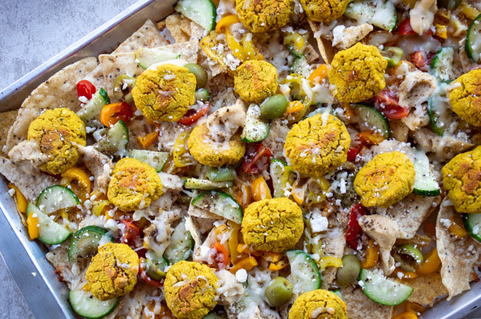 pan of nachos with falafel, hummus, and vegetables