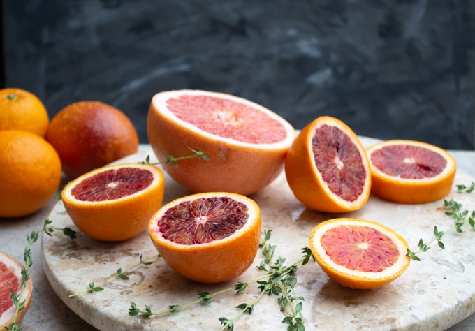 side view of sliced blood oranges and grapefruit and fresh thyme