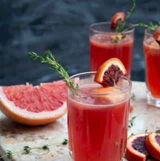 martha cocktail with blood orange and thyme garnish