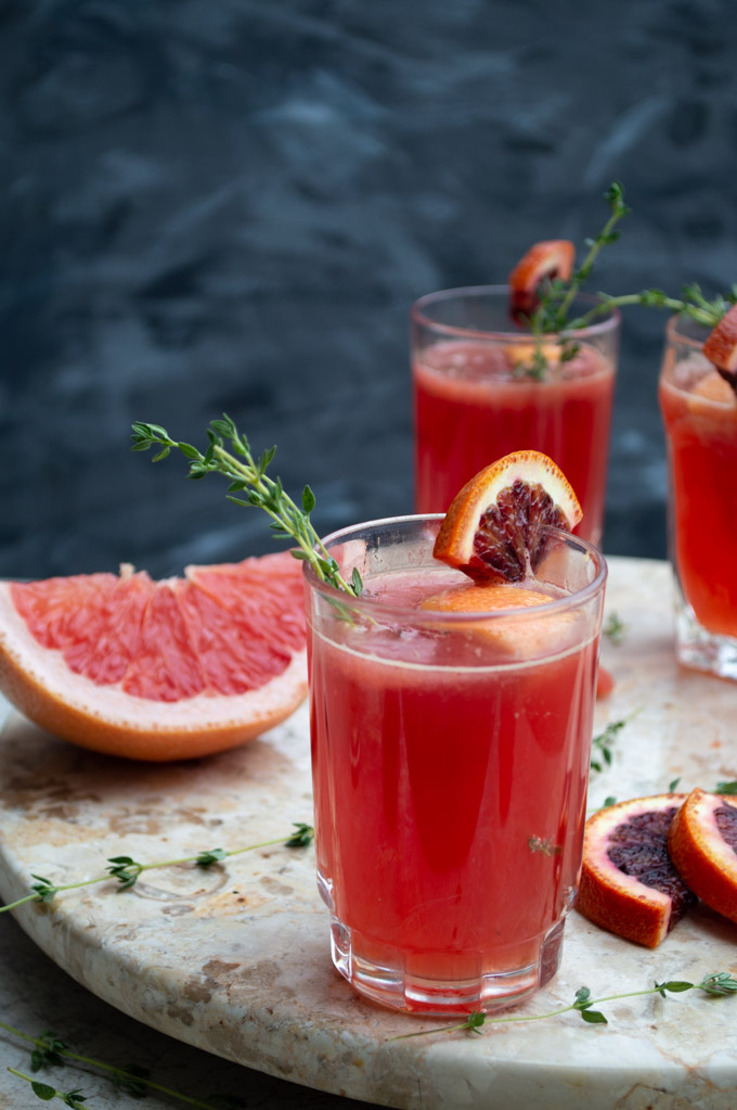 martha cocktail with blood orange and thyme garnish