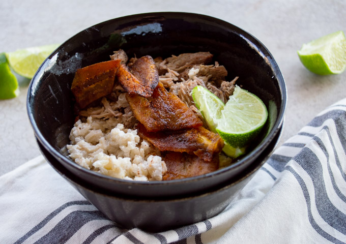 side view of black bowl of coconut rice, shredded pork, and fried plantains