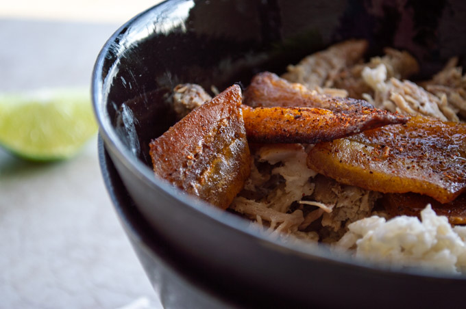 close up view of fried plantains in a black bowl