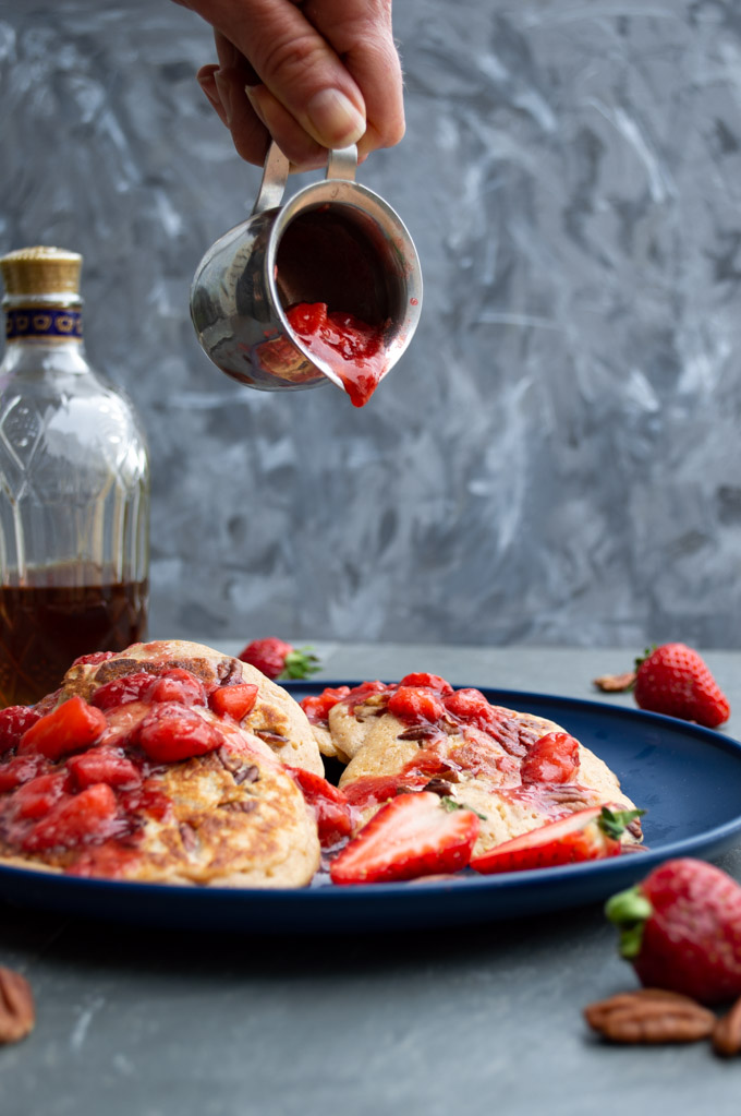 pouring strawberry bourbon syrup on cinnamon bourbon pecan pancakes
