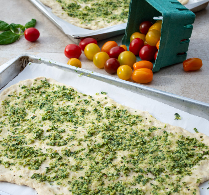 spreading pesto on pizza dough