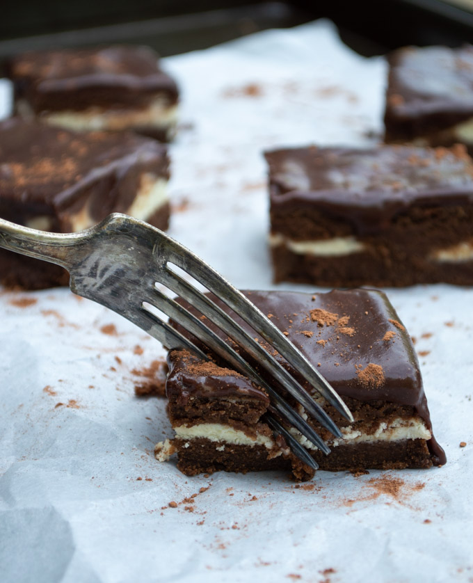 using a fork to slice a piece of fudge ribbon cake