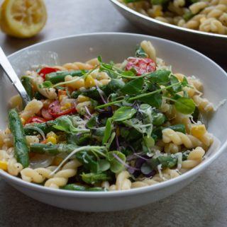 spring pasta in a white bowl with microgreens