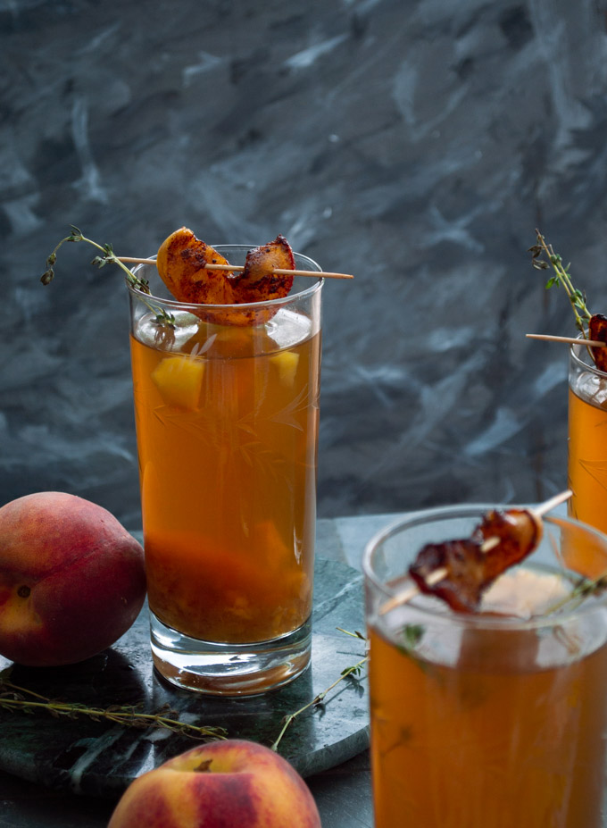 peach iced tea in back glass with peach slice