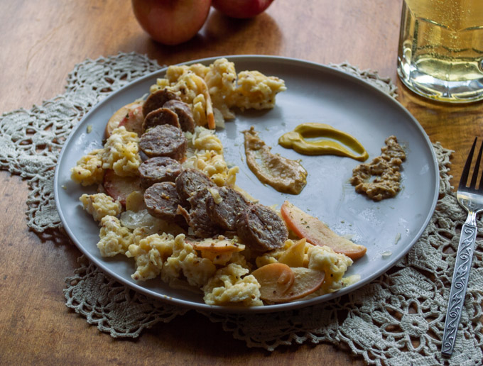 plate of german bratwurst, apples, and onions