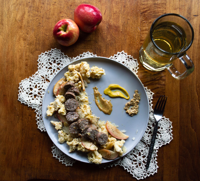 overhead view of german bratwurst, onions, and apples in a mustard cream sauce