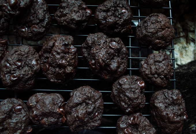overhead view of chocolate stout cookies cooling on a black metal rack